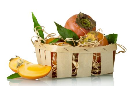 Ripe persimmons in a basket with hay and green leaves close-up isolated on a white background