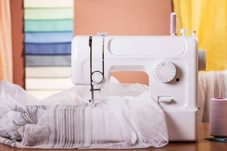 Household sewing machine with spools of thread and fabric samples in the background. Close-up shot.