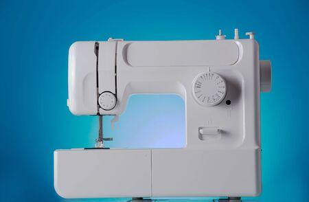 Modern sewing machine close-up on a blue background