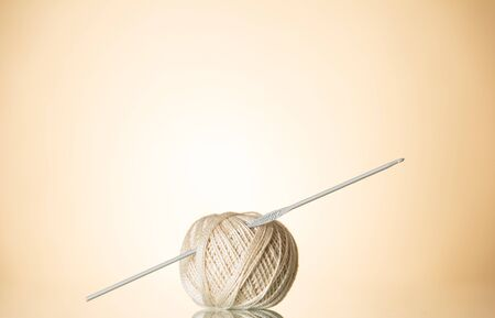 Ball of beige wool for knitting with a stuck knitting needle closeup on beige background
