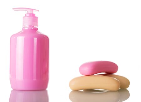 A bottle of pink liquid soap with a dispenser on one side of the bar of soap on the other. Close-up isolated on a white background.
