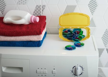 Folded towels, a bottle of fabric softener, and washing capsules folded on top of the washing machine. Close-up.