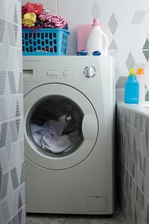 A washing machine in the bathroom, on which stands a basket of linen, washing powder and a bottle with a rinse aid. Standard-Bild