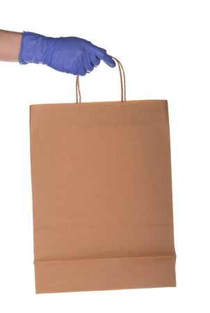 A courier's hand in a blue glove gives a paper bag. Shot close-up and isolated on a white background.