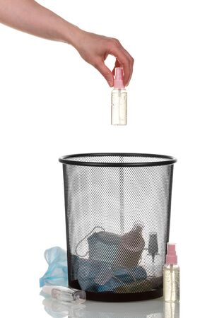 A female hand throws an empty bottle from the sanitizer into the trash with used masks, gloves and others. Isolated on a white background.