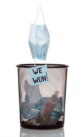 The used medical mask falls into the bin with bottles from sanitizers and the inscription we won. Coronavirus pandemic completion concept.