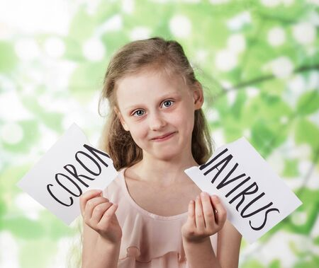 A girl on a background of green foliage holds a torn sheet with the inscription coronavirus. The concept of victory over coronovirus infection.