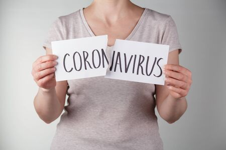 The concept of victory over the coronavirus. A woman in a beige T-shirt tears the inscription coronavirus closeup.