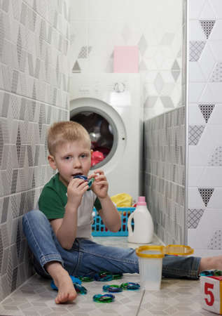 Child safety concept. Kid plays and eats deadly capsules for washing