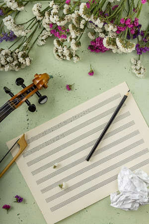 Top view. Musical creativity concept. Fictional sheet music, flowers and violin