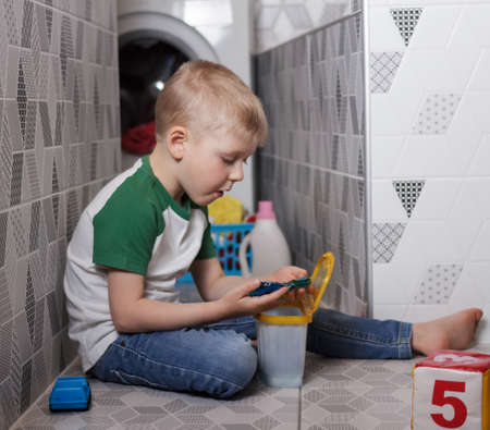 The concept of protecting children from chemical poisoning at home. Little boy playing with concentrated capsules for washing clothes in the bathroom 版權商用圖片