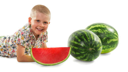 Little boy in a bright shirt lies near large whole watermelons and slices isolated on white background
