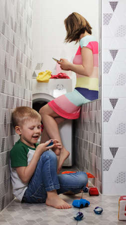 Danger of chemical poisoning in children. A child plays with capsules for washing while mom is distracted by talking on the phone