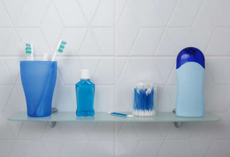 Shelf in a bright bathroom with oral care products and shower gel