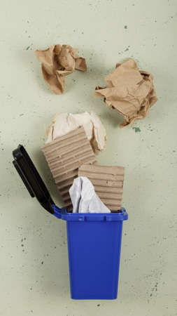 Sorting of household waste. Waste recycling. Waste bin in blue with various paper waste