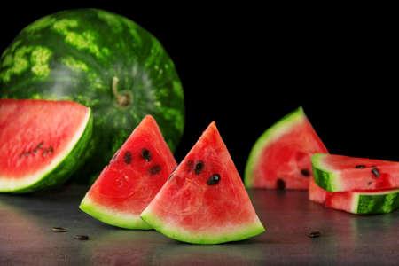 Fresh ripe watermelon and sliced pieces on a dark background. Low key photo 版權商用圖片