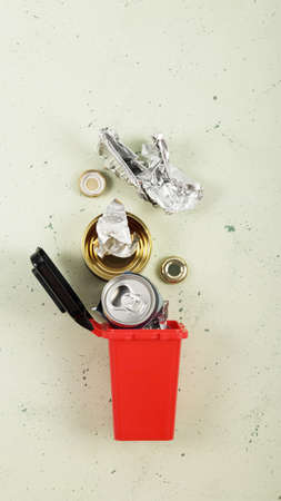 Sorting of household waste. Waste recycling. Waste container of red color with metal waste, beer cans 版權商用圖片