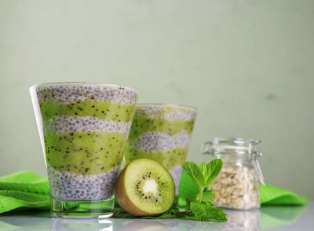 The concept of dietary proper nutrition. Protein-rich chia seeds in the form of a mousse with yogurt and kiwi puree on a light background