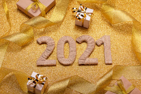 Bright golden postcard for the new year 2021, decorated with sparkling ribbon and gifts