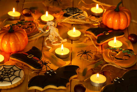 Halloween holiday. Gingerbread and other sweets, pumpkins, candles and symbols on a wooden table
