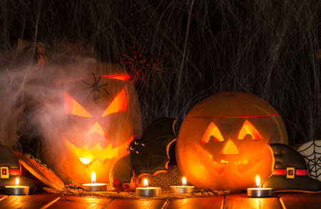 Two creepy Halloween pumpkins with a carved glowing grin. Gingerbread cookies and candles on a dark background with cobwebs 版權商用圖片