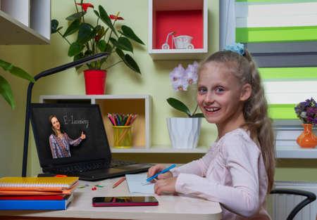 Distance learning concept. Happy girl runs the school program remotely using a laptop 版權商用圖片