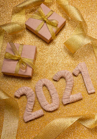 Sparkling New Year card. Gold background with craft gifts and ribbon, twine 2021 lettering 版權商用圖片