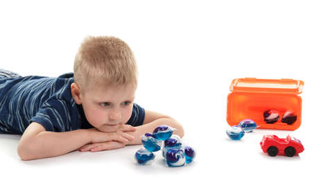 Little boy looking at capsules for washing, concentrated detergent isolated on white background 版權商用圖片