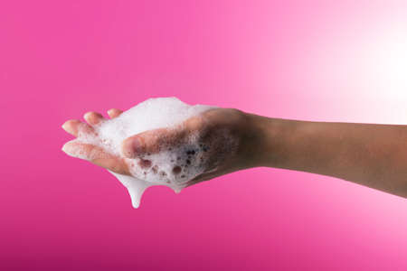Hand hygiene. Prevention of covid-19. Female hand in soapy foam on a pink background
