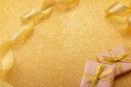 New Year's image for congratulations and inscriptions on a golden glowing background, decorated with gifts and ribbon