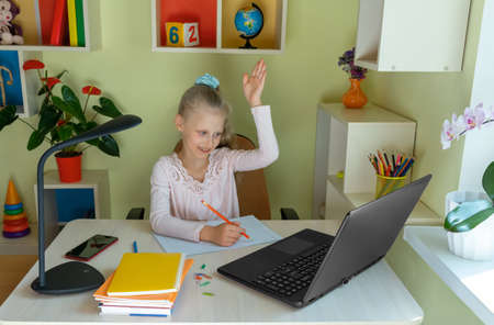 Distance learning concept. Girl communicates via laptop with her teacher while sitting at home