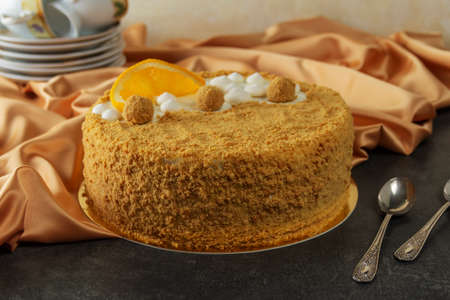 Orange honey cake on a background of golden fabric and tea cups with spoons 版權商用圖片