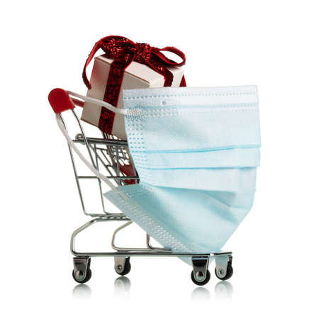 Personal protection mask on a wheelbarrow for shopping in a supermarket with bright new year gifts isolated on white background