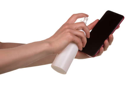 Disinfection of the phone. Female hands spray antiseptic on phone isolated on white background