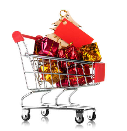 New Year's goods shopping concept. Shopping cart filled with colorful gifts isolated on white background