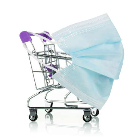 Concept of protecting people from coronavirus infection in stores and supermarkets. Shopping cart in protective mask isolated on white background