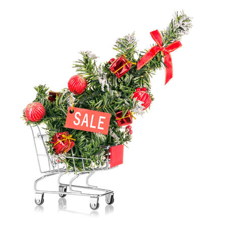 Christmas sale. Shopping cart in a supermarket with a Christmas tree and a sale tag isolated on a white background