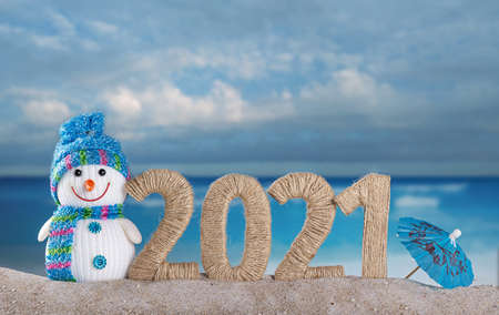 Happy snowman and the inscription 2021 in the sand on the beach against the background of the sea Stock Photo