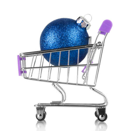 Small decorative shopping cart with blue christmas ball isolated on white background
