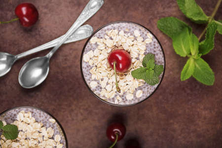 Healthy food concept. Dessert with oatmeal and chia seeds garnished with cherries. Top view