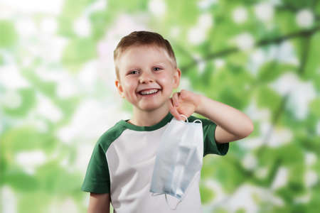 Happy little boy smiling and holding face mask in hand on green background Standard-Bild