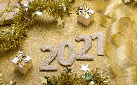 Top view. New Year card in gold colors. 2021 lettering decorated with ribbons and tinsel