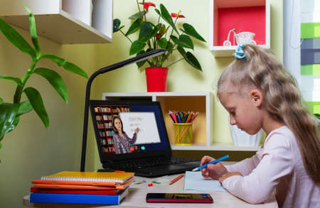 Little girl is engaged with her teacher using laptop