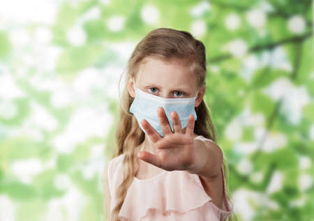 Stop! The concept of limiting the distance between people during the coronavirus. Little girl in protective mask