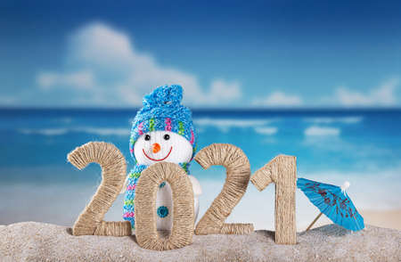 Decorative inscription 2021 in the sand on the beach decorated with a snowman on a sunny day