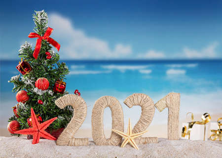 New year on the beach. Christmas tree, inscription 2021 on a sunny seaside Standard-Bild