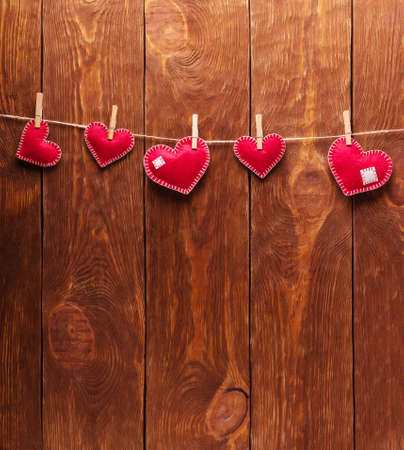 Concert for Valentine's Day. Red hearts made of felt pinned with clothespins to a string against the background of boards