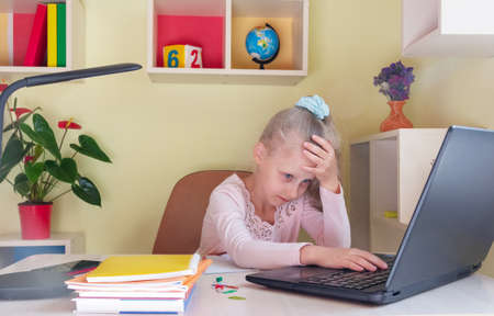 Sad schoolgirl is studying remotely on a laptop. Difficulties in perceiving information in remote learning Standard-Bild