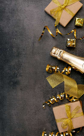 Top view. Golden gifts and ribbon, Christmas tinsel and bright gifts on a dark background