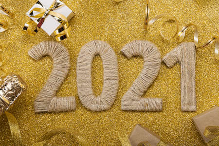 Lettering 2021 from handmade twine on gold with champagne bottle and ribbon